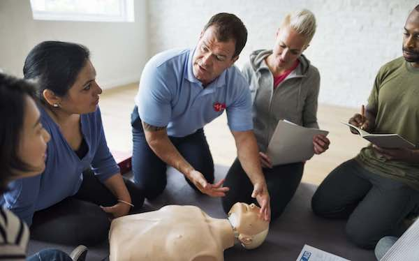 Instructor explaining CPR on CPR dummy