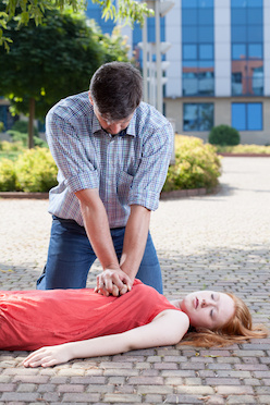 Man preforming CPR on woman